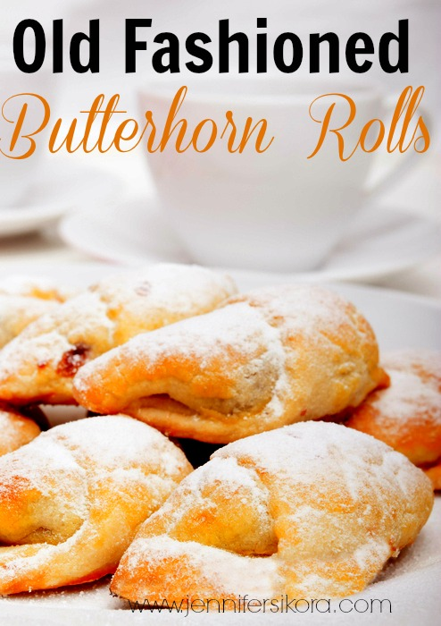 Closeup of homemade jam filled crescent rolls and white cups of tea