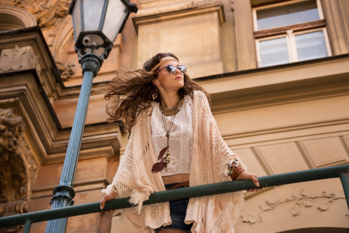 Longhaired hippy young lady in jeans shorts, knitted shawl and white blouse with sunglasses stands near streetlight in old town looking at skies