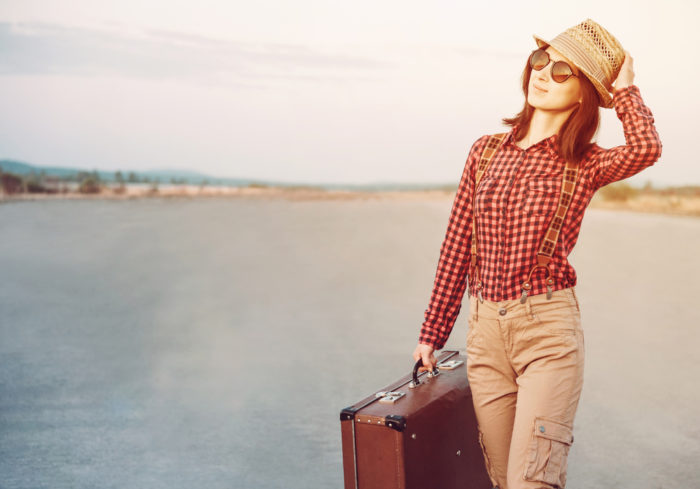 Traveler woman in hat and sunglasses with vintage suitcase, hipster style. With light effects